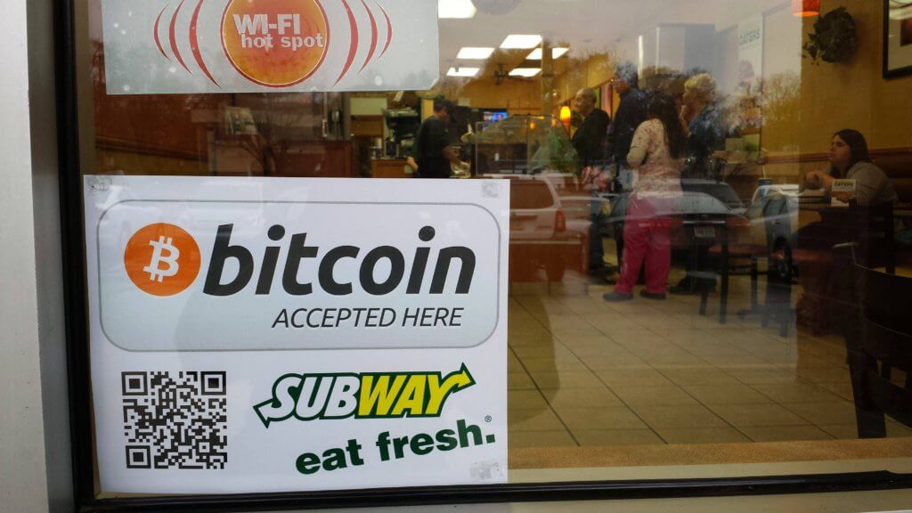 Shop window with sign saying they accept bitcoin