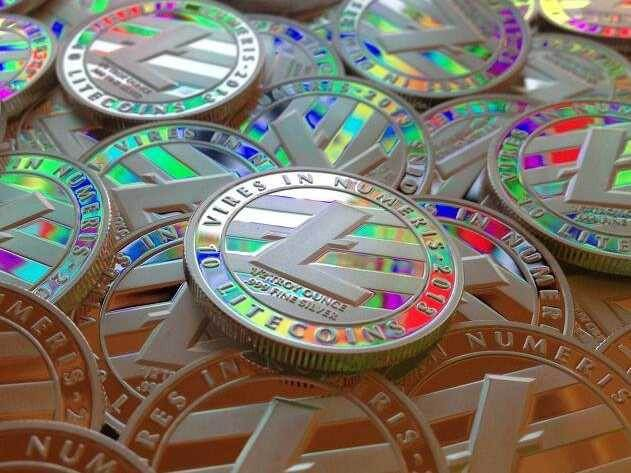 A pile of physical coins embossed with the litecoin logo